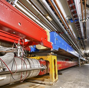 A long concrete tunnel with large blue and red scientific equipment on one side.